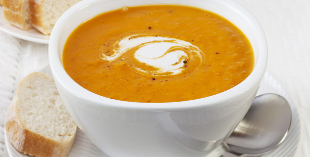 A bowl of spicy pumpkin soup, swirled with coconut cream.